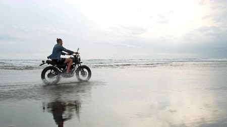 zvyk : Young handsome hipster man riding modern custom motorcycle racer on the black sand beach near the water. Surfing spot with ocean waves. Dostupné videozáznamy