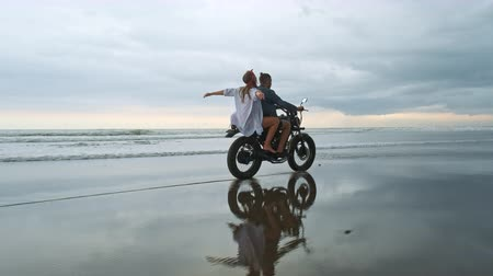 neşeli : Young beautiful couple hipsters riding retro motorcycle on the beach, outdoor portrait, riding guy and girl, travel together, ocean, sea