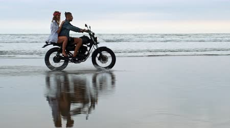 Young beautiful couple hipsters riding retro motorcycle on the beach, outdoor portrait, riding guy and girl, travel together, ocean, sea