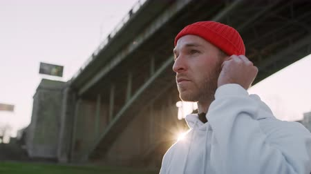 Portrait handsome young guy sportsman looking sideways wearing headphones sports clothes running outside listen music sunset stand sport fitness man technology training workout sunlight slow motion
