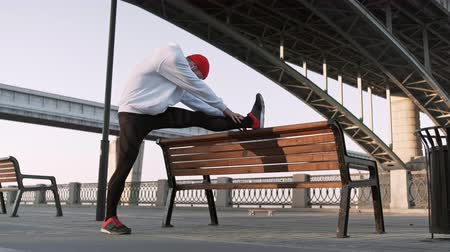 Young man stretching his arm muscles under the bridge before running. Handsome athlete male doing stretching exercise, preparing for workout. Fitness concept.