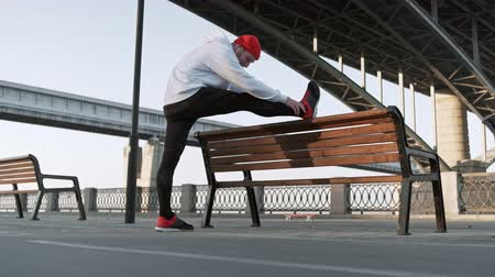 cardio workout : stretch man training urban. Young flexible male stretches deeply in urban city surroundings, in slow motion Stock Footage