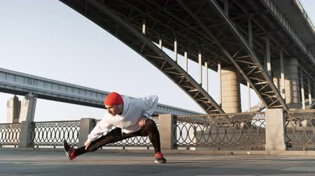 stretch man training urban. Young flexible male stretches deeply in urban city surroundings, in slow motion Vídeos