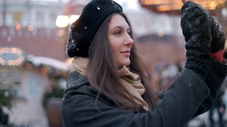 Woman take photo on Christmas tree decoration . A beautiful young woman or girl doing selfie or using phone emotionally outdoors in front of Christmas holidays decorations. Dostupné videozáznamy