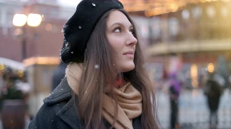 Portrait of beautiful smiling young woman outside enjoying winter snowfall wearing glasses cap and coat looking at camera. Dostupné videozáznamy
