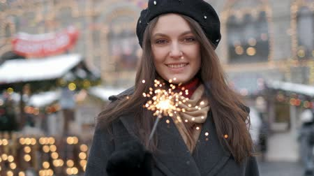 Holiday, Christmas and people concept - Young happy woman wearing Santa suit holding bengal light over Christmas city center background