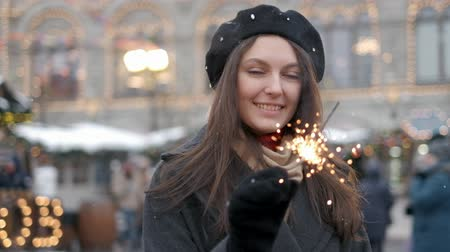 кошачий : Cheerful young woman holding sparklers in hand outdoor. Detail of girl celebrating new year s eve with bengal light. Closeup of beautiful woman holding a sparkling stick at bokeh cities centre