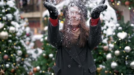 scatters : SLOW MOTION: Young woman blowing snow. Young woman blowing snow. Portrait of cute young woman blowing on snow in her hands. Snow scatters in different directions Stock Footage