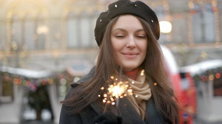 Outdoor of young beautiful happy smiling girl holding sparkler, walking on street. Model looking up, wearing stylish winter clothes. Waist up. Christmas, New Year, concept. Magic snowfall. Toned Dostupné videozáznamy