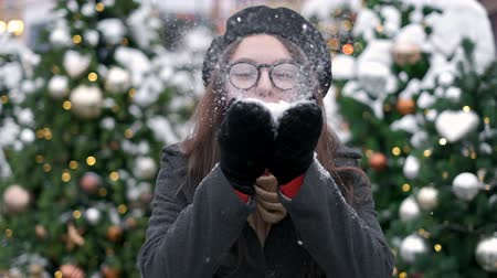 Beauty Winter Girl Blowing Snow in city center. Outdoors. Flying Snowflakes. Joyful Young woman Having Fun. Winter and Christmas time concept Dostupné videozáznamy