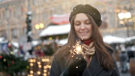 Cheerful young woman holding sparklers in hand outdoor. Detail of girl celebrating new year s eve with bengal light. Closeup of beautiful woman holding a sparkling stick at bokeh cities centre