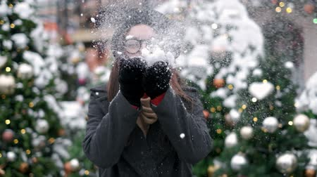 SLOW MOTION: Young woman blowing snow. Young woman blowing snow. Portrait of cute young woman blowing on snow in her hands. Snow scatters in different directions Dostupné videozáznamy