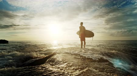 плавники : A man is standing with a surf in his hands on the sea shore.