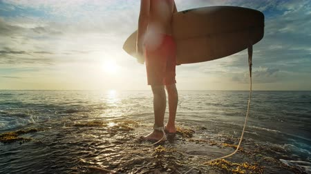 A man is standing with a surf in his hands on the sea shore.