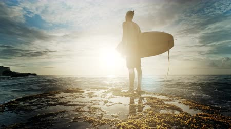 barışçı : A man is standing with a surf in his hands on the sea shore.