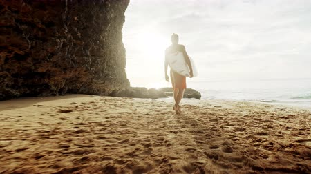 Young man surfer in wetsuit picks up surf board at the beach walking on the sand along sea shore looking at the ocean at sunset gimbal dolly steadycam Dostupné videozáznamy