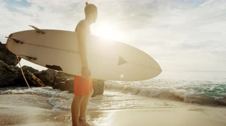 lifestyles : A man is standing with a surf in his hands on the sea shore.