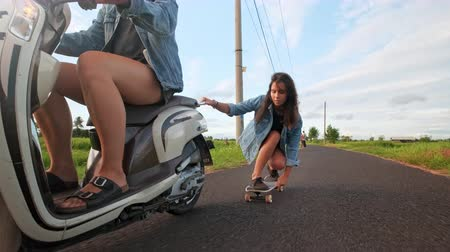 longboard : Group of friends skating and motorcycling. Cheerful teenagers having fun outdoors. Two women riding on a sunny day. Happy young couple having fun with skateboard on the road. Stock Footage