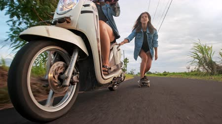 Group of friends skating and motorcycling. Cheerful teenagers having fun outdoors. Two women riding on a sunny day. Happy young couple having fun with skateboard on the road. Dostupné videozáznamy