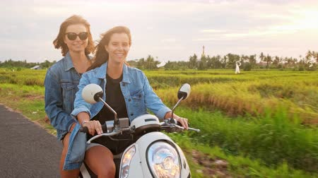 захватывающий : Young attractive couple of fashionable hipsters or millennials driving towards new exciting travel destination on motorbike on mountain forest road.