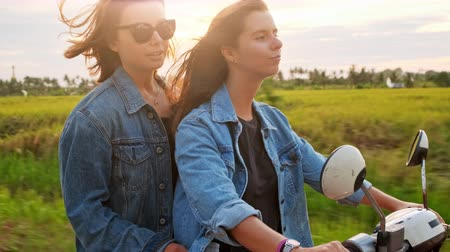 Young attractive couple of fashionable hipsters or millennials driving towards new exciting travel destination on motorbike on mountain forest road.