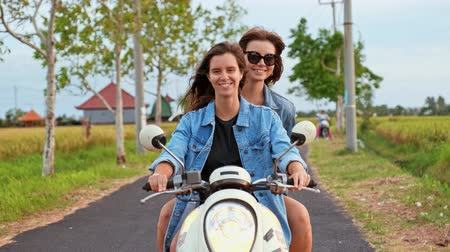 Joyful young women traveling by motorbike. Two cheerful laughing girlfreinds motorbike travelers portrait behind the sunset sea coast Dostupné videozáznamy
