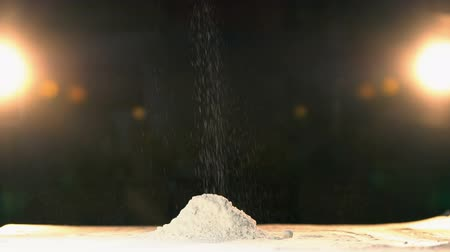 мучной : Hand throwing flour in a heap rapid. Hand throws white powder mountain slow mo. a handful of cocaine slowmotion. Endless drugs on a black background in slow motion. Sugar or salt on a white table. Стоковые видеозаписи