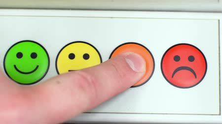 gömbölyű : 4 in 1. The finger presses on emoticons with different emotions. A person chooses his mood. A man switches from sadness to happiness. A group of buttons with an image of smiles 4k. Stock mozgókép