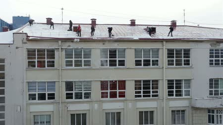 clearing away : Many men throw white snow from the roof of a multi-storey building. Heavy seasonal male labor. People work as a shovel. Utilities in action. Snow falls from the roof. Stock Footage