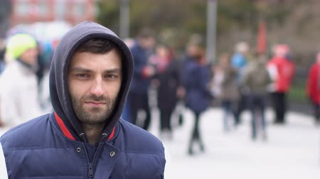 into focus : A man with a stubble looks into the camera. Closeup of a real confident boy in outdoors. Close-up of a young adult man in a hood. The police are walking.