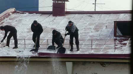 excesso de trabalho : NOVOSIBIRSK, RUSSIA, FEBRUARY 23, 2017: Many men throw white snow from the roof of a multi-storey building. Heavy seasonal male labor. People work as shovel. Guy quickly clean the roof of excess snow. Vídeos