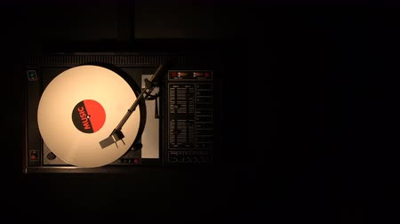 rpm : Vinyl record on the pleer. Plays a song from an old turntable 4k top view. Black background. The music round plate rotate. Music disc turn. Obsolete technology. Music began to sound. Start the Player.