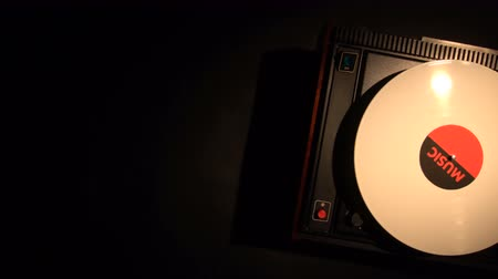 rpm : Vinyl record on the pleer. Plays a song from an old turntable 4k top view. Black background. The music round plate rotate. Music disc turn. Obsolete technology. White object with place for titles. Stock Footage