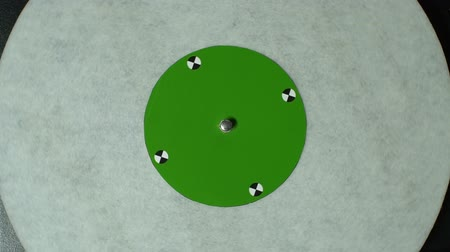 rpm : Vinyl record pleer. Plays song from an old turntable 4k top view. Black background. Music round plate rotate. Music disc turn. Tracking shot rotating disk with chroma-key green screen. Tracking point.