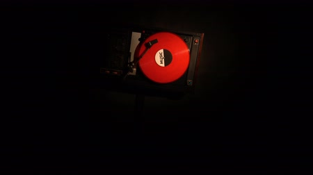 rock album : Vinyl record on the pleer. Plays a song from an old turntable 4k top view. Black background. The music round plate rotate. Music disc turn. Obsolete technology. The red object and camera rotates.