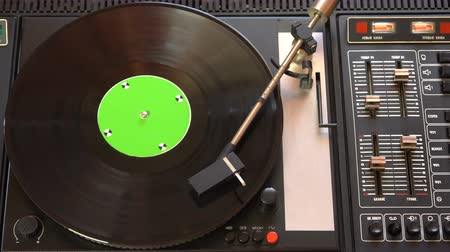 płyta winylowa : Vinyl record pleer. Plays song from an old turntable 4k top view. Black background. Music round plate rotate. Music disc turn. Tracking shot rotating disk with chroma-key green screen. Tracking point.