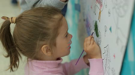 рисунки : Kids drawing on wallpaper with paints Стоковые видеозаписи