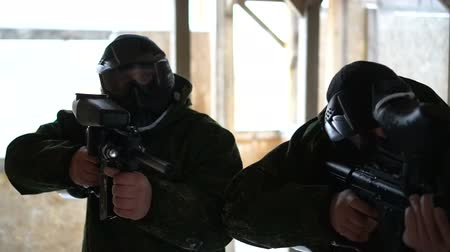 professional paintball : Men in uniform shooting with paintball guns