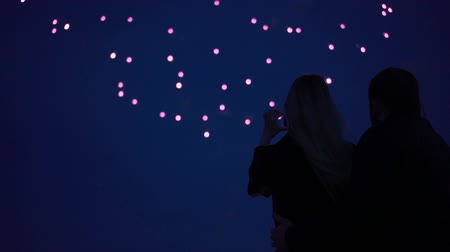 pirotecnia : Silhouette of a loving couple of people looking at the fireworks.