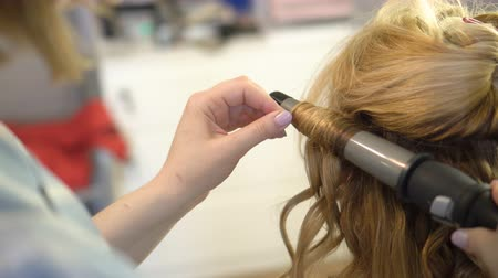 ringlet : A stylist makes a hairstyle to a woman curling her hair curling up closeup. Stock Footage
