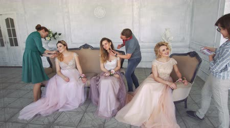 ориентация : Stylists and make-up artists paint girls in a white studio.