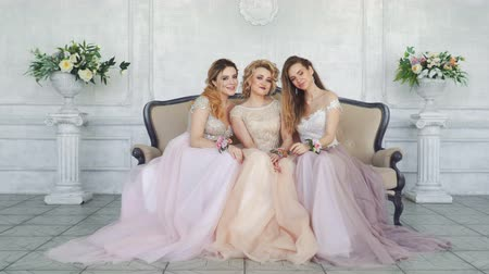 браслет : Young adult girls sit in pink and purple dresses and look at the camera Стоковые видеозаписи