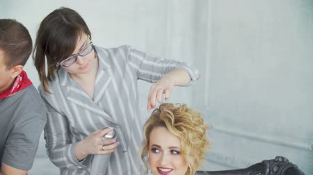 uzun saçlı : The stylist is making a hairstyle in the salon of a girl. Stok Video