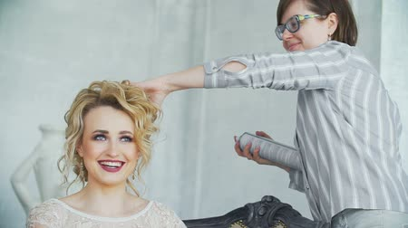 uzun saçlı : Spray in the hand of stylist treats the blond hair in slowmo. Stok Video