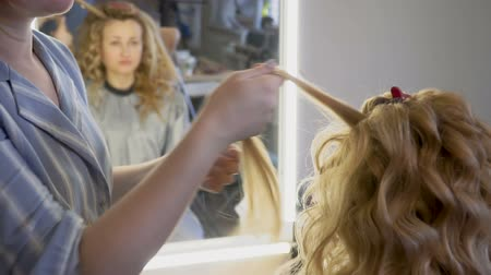 ondulação : A stylist makes a hairstyle to a woman curling her hair curling up closeup. Vídeos