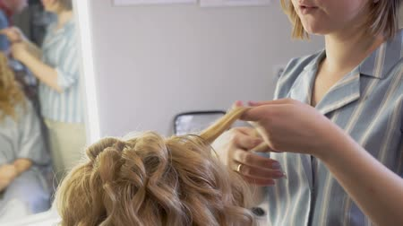 колечко : A stylist makes a hairstyle to a woman curling her hair curling up closeup. Стоковые видеозаписи