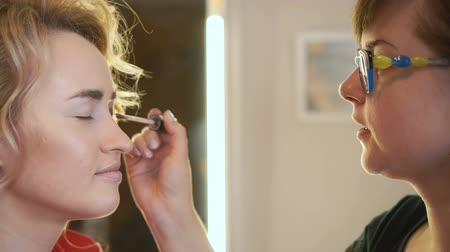 daily : The make-up artist paints the eyes of the girl with a brush close-up.