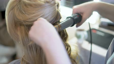 curling hair : Stylist Makes a Hairstyle to a Woman Curling Her Hair Curling up.