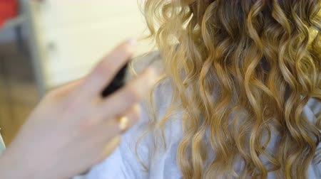 ringlet : Stylist Makes a Hairstyle to a Woman Curling Her Hair Curling Up. Stock Footage