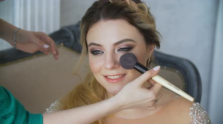bronz : The Make-up Artist Paints the Eyes of the Girl with a Brush.